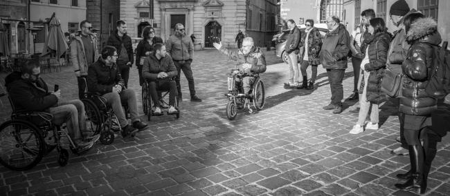 Gruppo di persone in una piazza alcune in piedi alcune in carrozzina durante una formazione