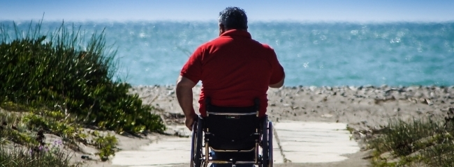 Persona disabie in carrozzina davanti al mare