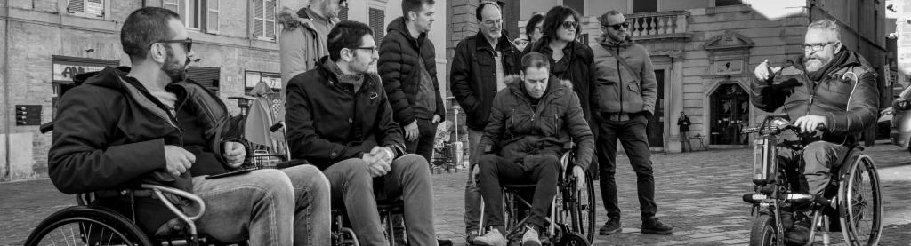 Roberto Vitali Guida un gruppo di persone in carrozzina e a piedi in visita a una città