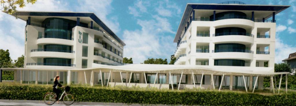 Una persona in bicicletta passa davanti al nuovo hotel Blu Suite Bellaria costituito da due edifici affiancati e connessi tra loro al piano terra